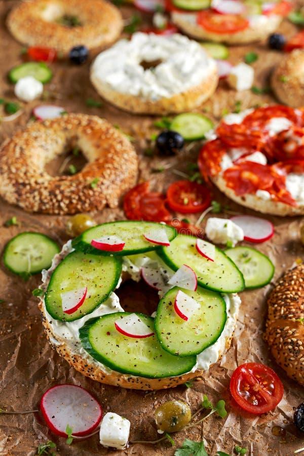 Sanduíches deliciosos do Bagel com queijo macio, chouriço, vegetais Foco selecionado fotografia de stock