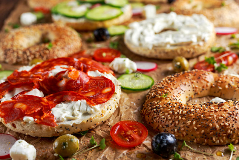Sanduíches deliciosos do Bagel com queijo macio, chouriço, vegetais Foco selecionado foto de stock royalty free