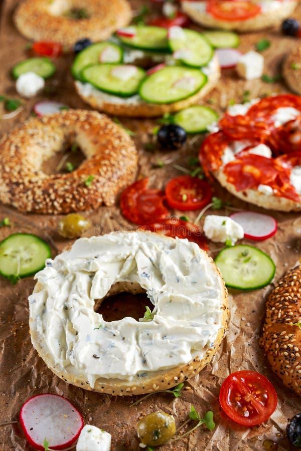 Sanduíches deliciosos do Bagel com queijo macio, chouriço, vegetais Foco selecionado imagem de stock royalty free