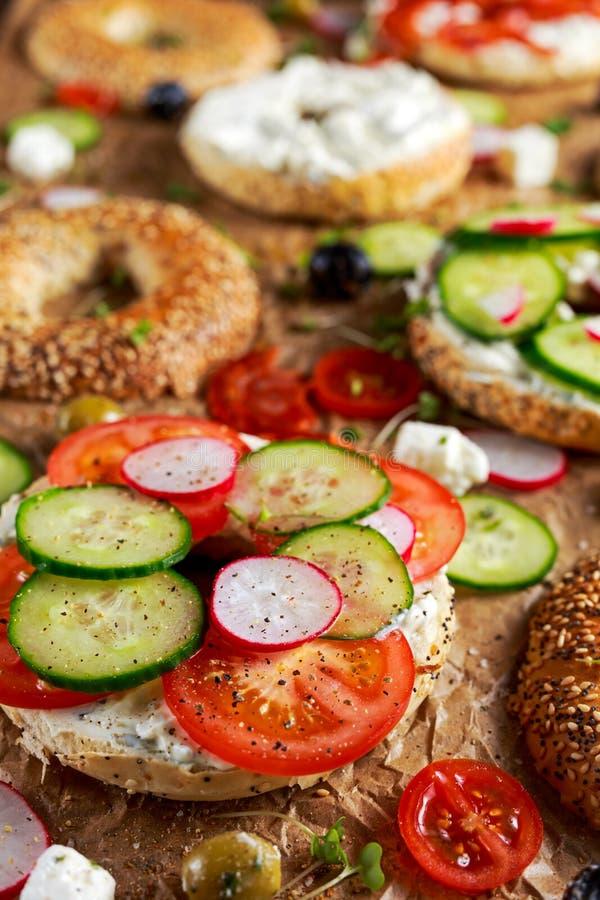 Sanduíches deliciosos do Bagel com queijo macio, chouriço, vegetais Foco selecionado fotografia de stock royalty free