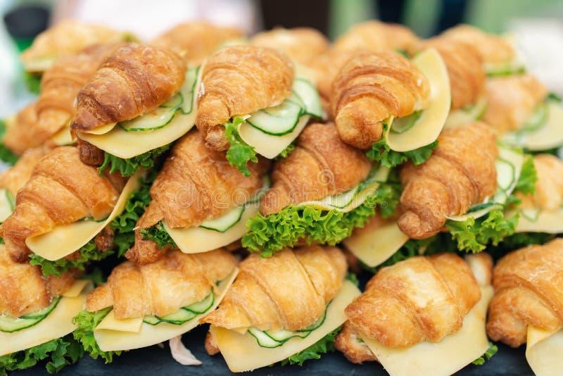 Sanduíches deliciosos dos croissant com pepino fresco, queijo, o ovo cozido duro e a salada imagens de stock royalty free