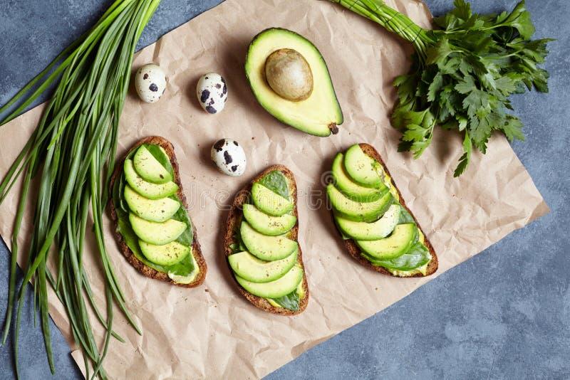 Sanduíches do abacate com guacamole e espinafres no papel de pergaminho em um fundo concreto Alimento da mola Baixa dieta do carb imagem de stock royalty free
