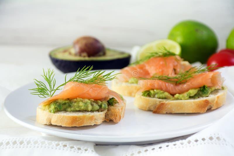 Sanduíches do Baguette com salmão fumado e creme ou guac do abacate imagem de stock