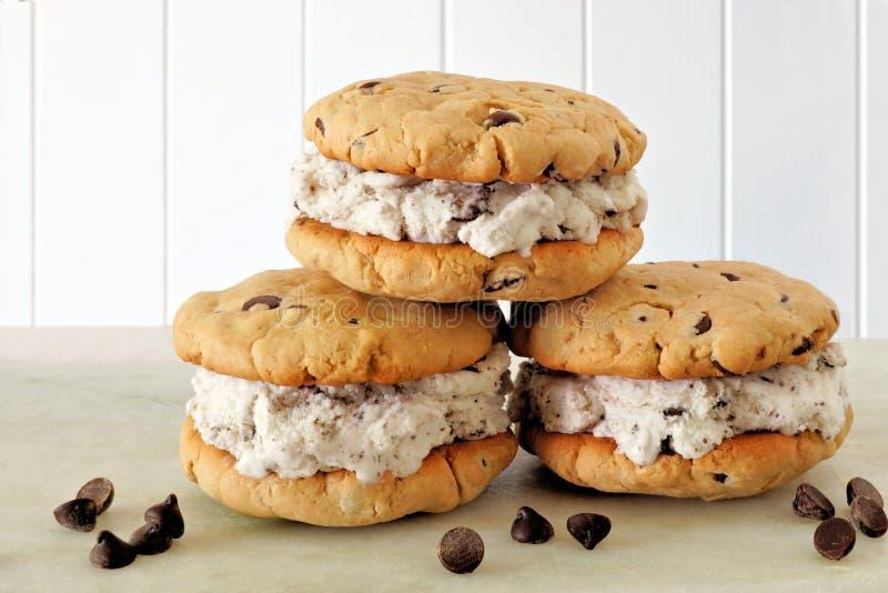 Sanduíches do gelado da cookie dos pedaços de chocolate sobre a madeira branca imagem de stock