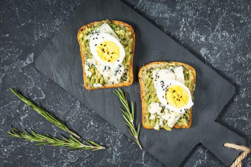 Sanduíches do ovo e do abacate com queijo creme para o café da manhã saudável no fundo de pedra imagem de stock
