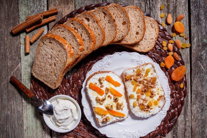 Sanduíches do pão de centeio com queijo creme, frutos secados, porcas imagem de stock