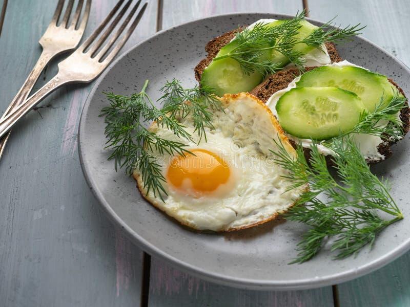 Sanduíches do requeijão e fatias e ovos mexidos frescos do pepino para um café da manhã claro em uma bandeja da prancha de turque imagens de stock royalty free