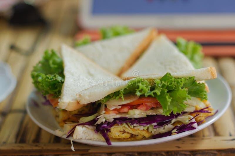Sanduíches e batatas fritas vegetais do triângulo em uma tabela de madeira em r foto de stock