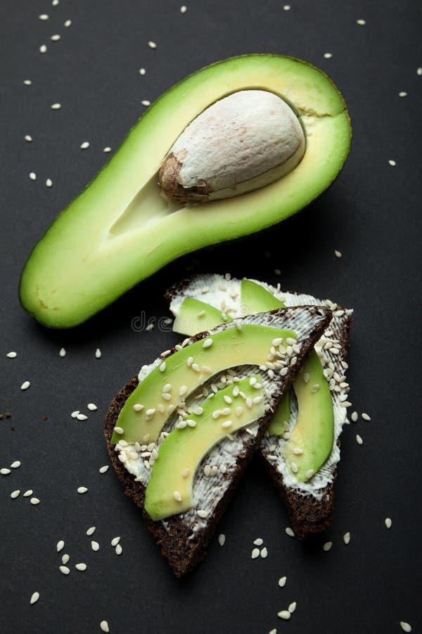 Sanduíches frescos e dietéticos do abacate em um fundo preto imagens de stock royalty free