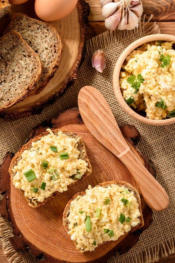 Sanduíches inteiros do trigo com ovo e queijo de barrar no coto de madeira foto de stock