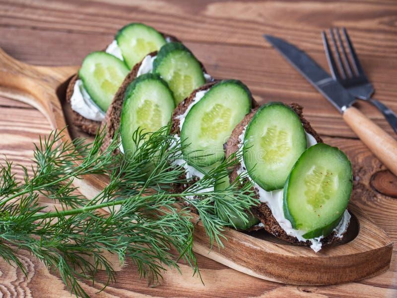 Sanduíches no brinde do pão de centeio com queijo creme e o pepino fresco com um ramo do aneto em uma bandeja da vila fotografia de stock