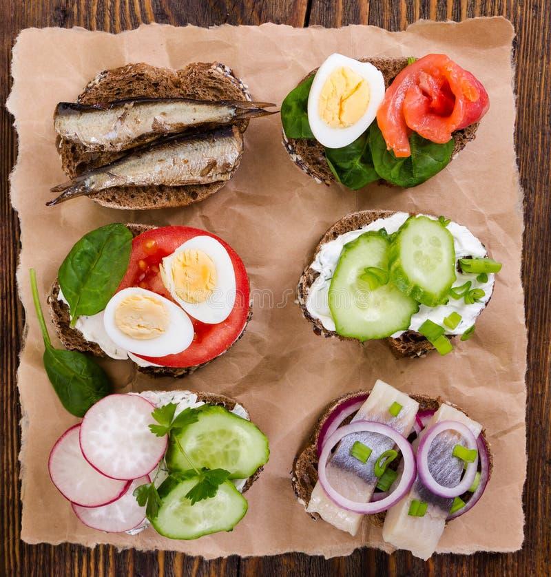 Sanduíches pequenos no fundo de madeira Vista superior imagem de stock