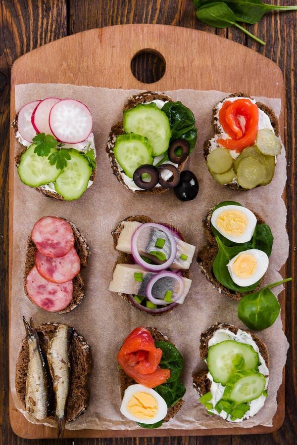 Sanduíches pequenos no fundo de madeira Vista superior imagens de stock royalty free