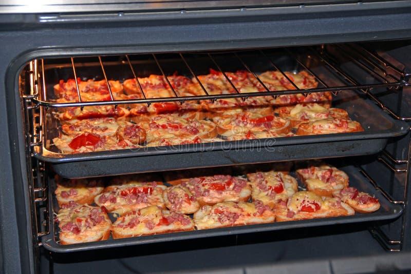 Sanduíches quentes com a salsicha e o queijo derretido que cozinham na placa de identificação Cozinhando o prato saboroso fotografia de stock