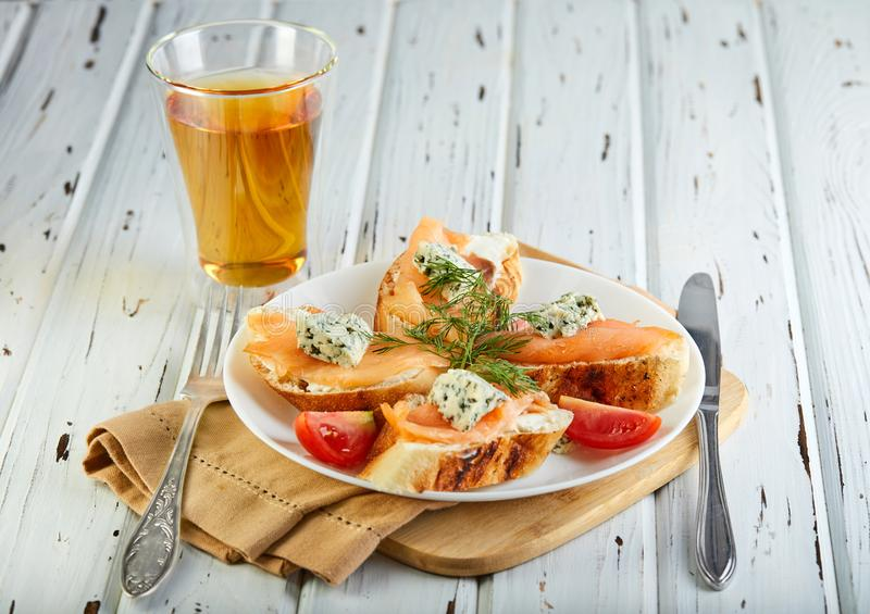 Sanduíches saborosos do café da manhã com os tomates dos salmões e do queijo e de cereja em um branco de madeira imagens de stock