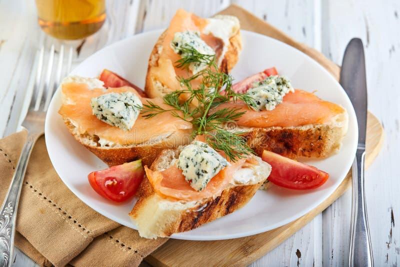 Sanduíches saborosos do café da manhã com os tomates dos salmões e do queijo e de cereja em um branco de madeira imagem de stock