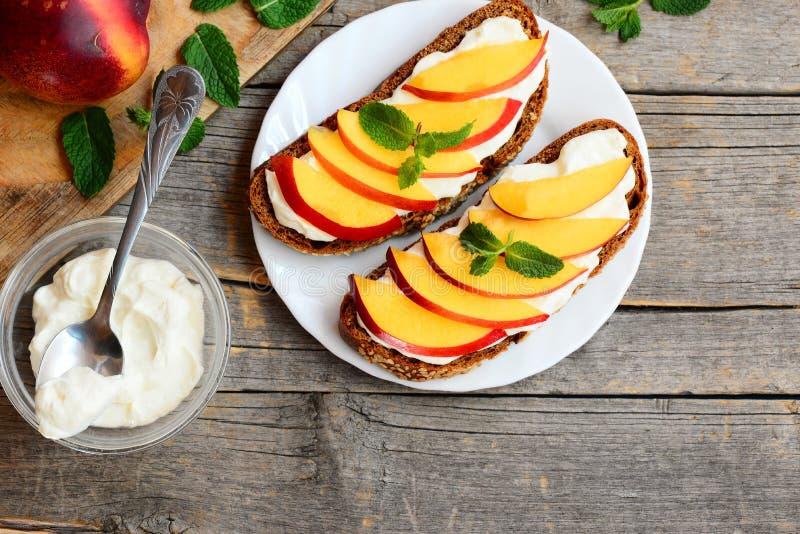Sanduíches simples do centeio com queijo macio e fatias frescas das nectarina Sanduíches brilhantes do verão em uma placa Fundo d imagem de stock royalty free