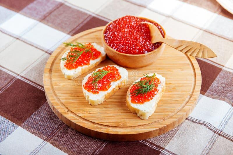 Sanduíches vermelhos do caviar na placa no fundo de madeira imagem de stock