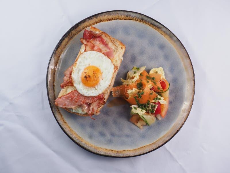 Sandu?che com um ovo frito, um bacon, um queijo e uns vegetais imagens de stock royalty free