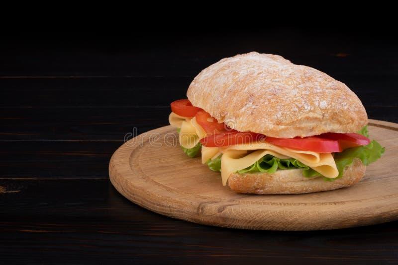 Sandu?che de Ciabatta com alface, prosciutto e queijo na placa de madeira com espa?o da c?pia fotos de stock royalty free