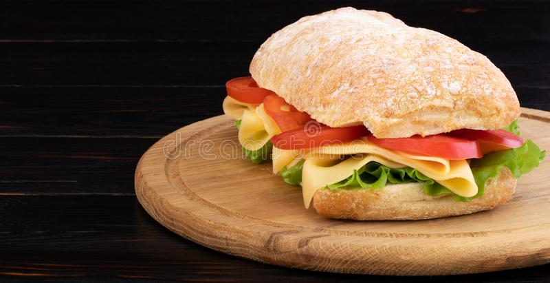 Sandu?che de Ciabatta com alface, prosciutto e queijo na placa de madeira com espa?o da c?pia imagem de stock royalty free