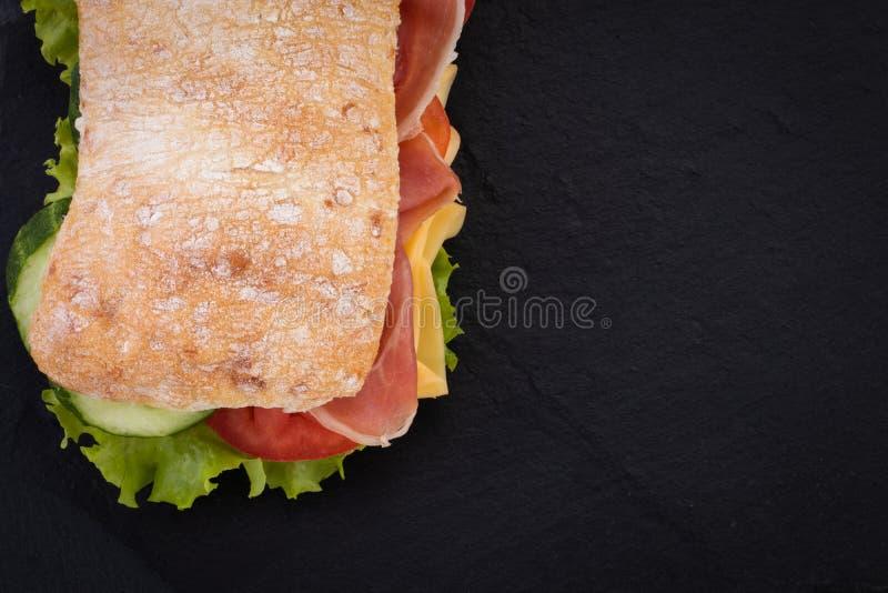 Sandu?che de Ciabatta com alface, prosciutto e queijo sobre o fundo de pedra Vista superior com espa?o da c?pia imagem de stock