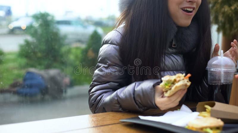 Sandu?che guardando f?mea feliz que come o caf? do jantar, encontro da pessoa desabrigada exterior imagem de stock