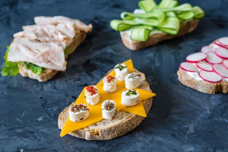 Sandu?ches abertos saud?veis com pastrami dos vegetais, das cenouras, do rabanete, do queijo cheddar e do peru, pepino em um fund foto de stock royalty free
