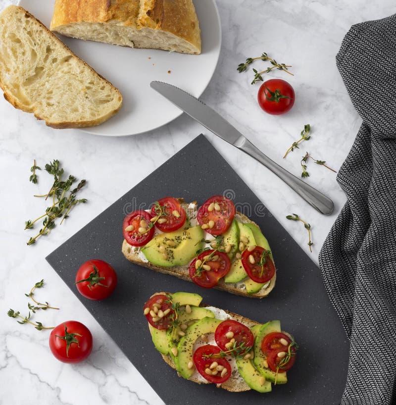 Sandu?ches caseiros com abacate, tomates e tomilho do queijo creme com azeite fotografia de stock royalty free