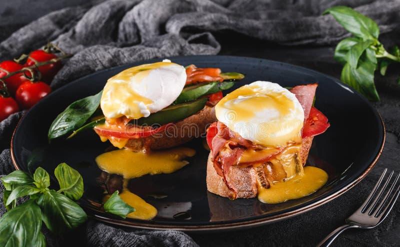 Sandu?ches saud?veis do caf? da manh? Brindes do pão com ovos escalfados ou ovos Benedict, legumes frescos, abacate imagens de stock