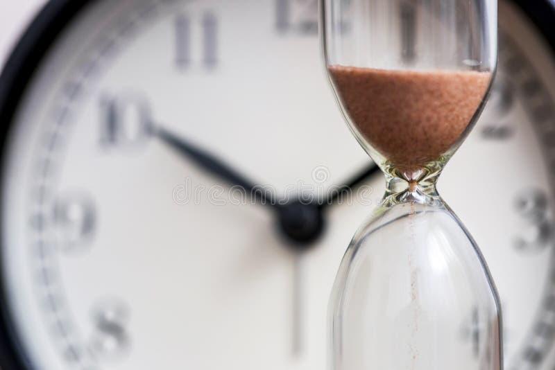 Sanduhr auf dem Hintergrund der Bürouhr als Zeit, die unzeitgemäß Konzept für Geschäftsfrist, -dringlichkeit und -betrieb verstre stockbild