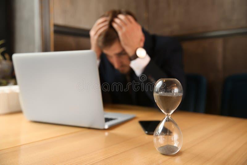 Sanduhr auf Tabelle des gestörten Geschäftsmannes, der im Café sitzt stockfotografie
