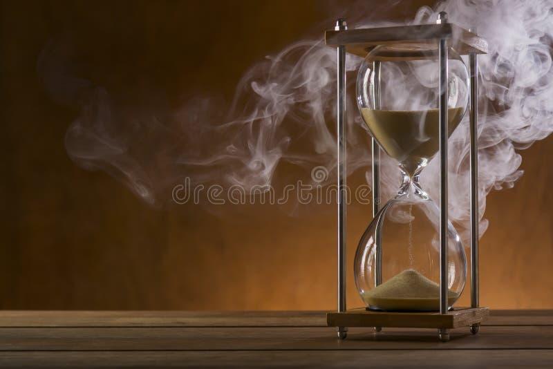Sanduhr und Rauch auf einem Holztisch stockfotografie