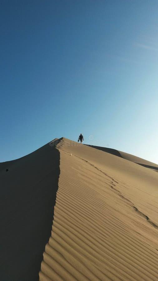 Sandunes en AIC, Perú Un hombre que camina en la distancia sobre el rigde de una duna de arena fotos de archivo