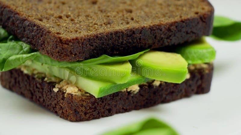Sandwich à avocat sur le pain de seigle foncé fait avec le fromage coupé en tranches frais d'avocat, d'épinard et fondu images libres de droits