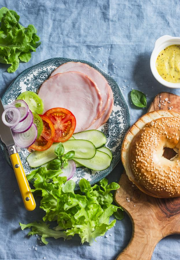 Sandwich à bagel avec du jambon de dinde, les légumes et la salade verte sur un fond bleu, vue supérieure, configuration plate No image libre de droits