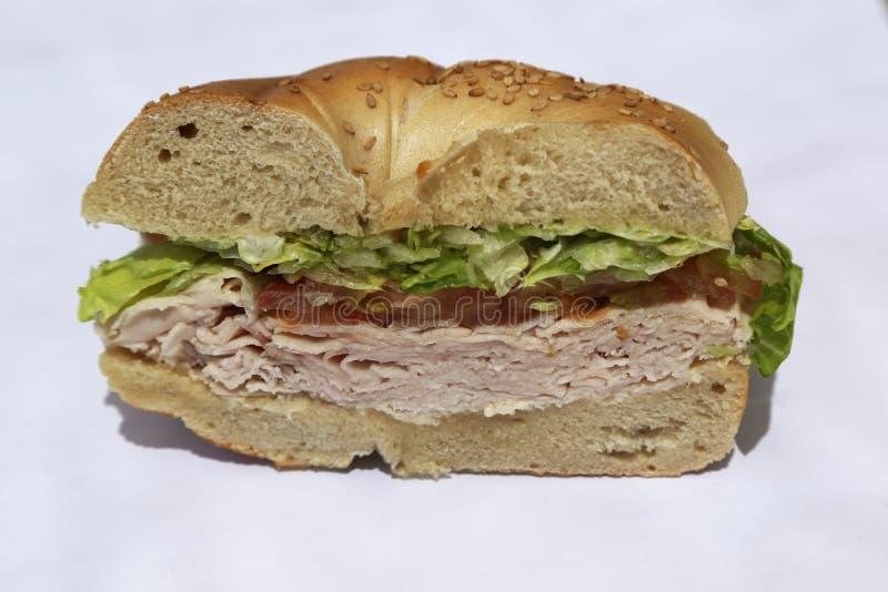 Sandwich à bagel avec le blanc de dinde, la laitue et la tomate image libre de droits