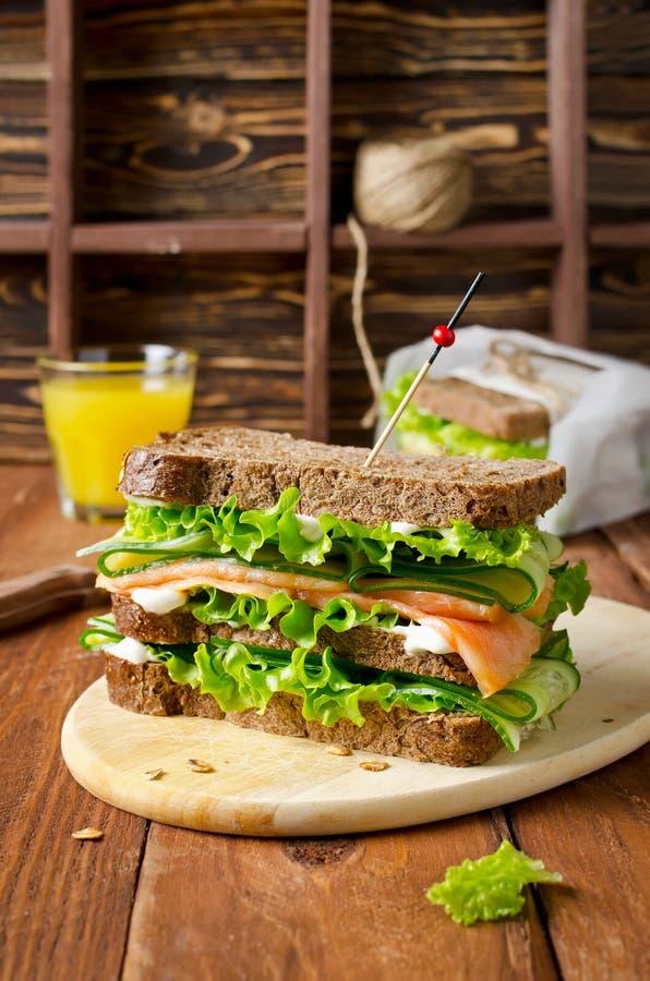 Sandwich à club avec des saumons et des concombres image stock