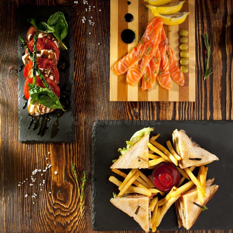Sandwich à club, salade de Caprese et saumons traités photo stock