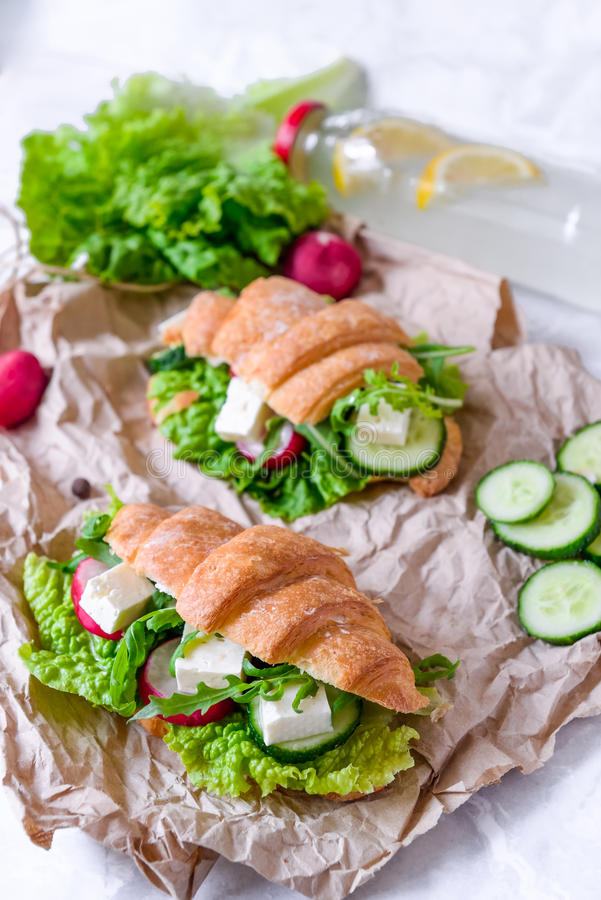 Sandwich à croissant avec du fromage et des légumes pour le casse-croûte, le papier de métier et le fond sains de verts Nourritur photo libre de droits