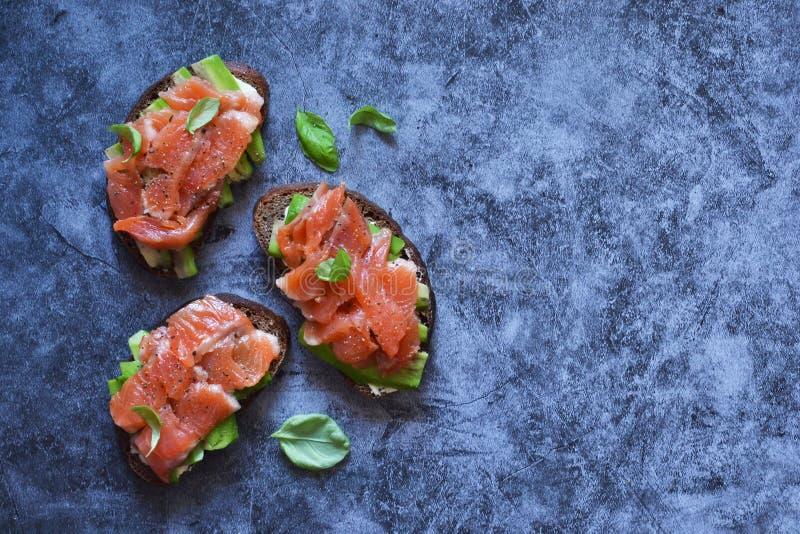 Sandwich à l'avocat et au saumon sur fond de béton Vue depuis le haut image stock