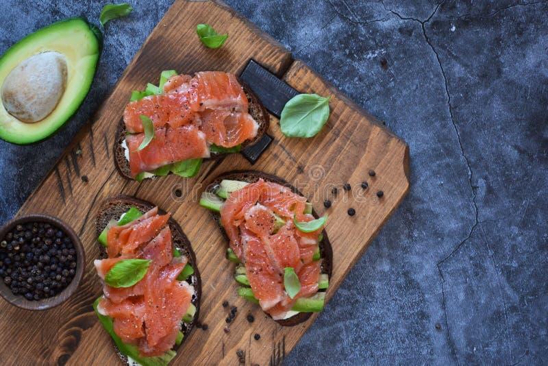 Sandwich à l'avocat et au saumon sur fond de béton Vue depuis le haut photographie stock libre de droits
