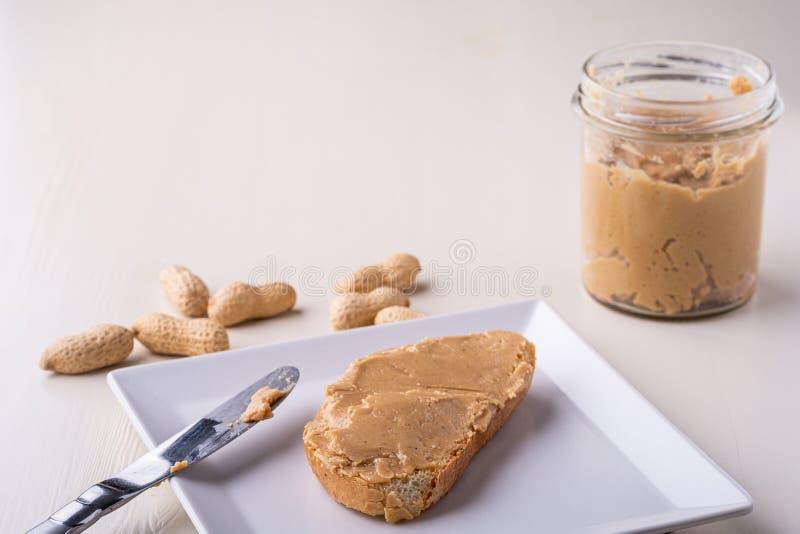 Sandwich à pain de beurre d'arachide sur le fond en bois formé carré blanc de couteau de table d'écrou d'arachides de plat images libres de droits