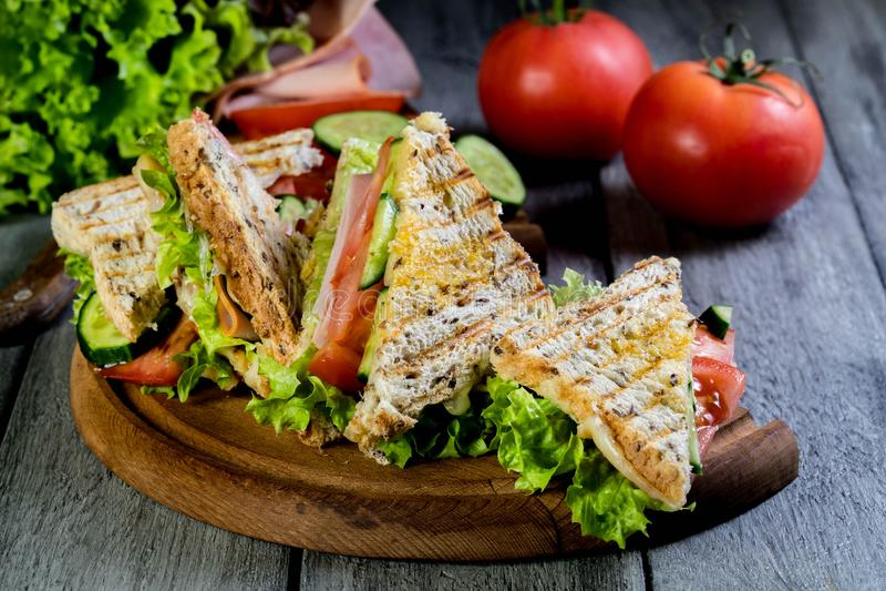 Sandwich à Panini avec du jambon, la tomate et la laitue photo libre de droits
