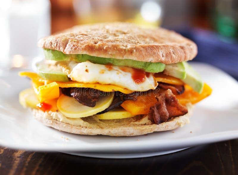 Sandwich à petit déjeuner avec l'oeuf, le lard, l'avocat et les légumes photos libres de droits