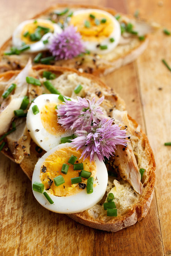 Sandwich with adition of mackerel fish , eggs and edible flowers of chives on wooden table. Healthy and nutritious sandwich with adition of mackerel fish , eggs stock image
