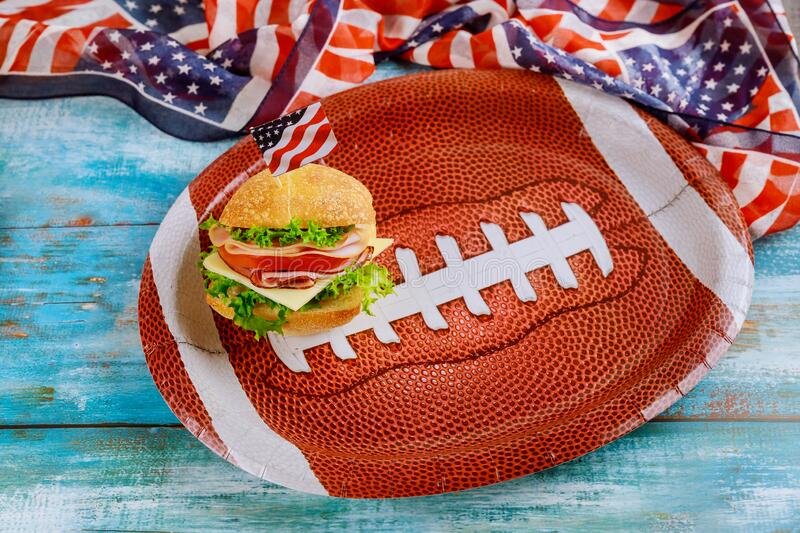 Sandwich on american football ball plate with american flag stock photo