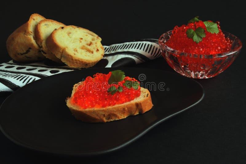 Sandwich appétissant avec le caviar saumoné rouge du plat en céramique noir, de la baguette blanche sur la serviette de papier av photos libres de droits