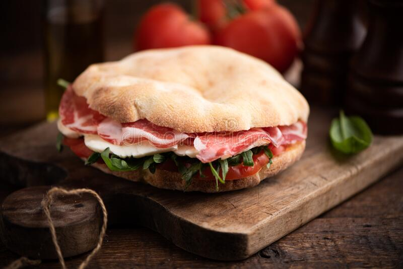 Sandwich from arab bread with lettuce rucola, slices of fresh tomatoes,cheese and ham royalty free stock image