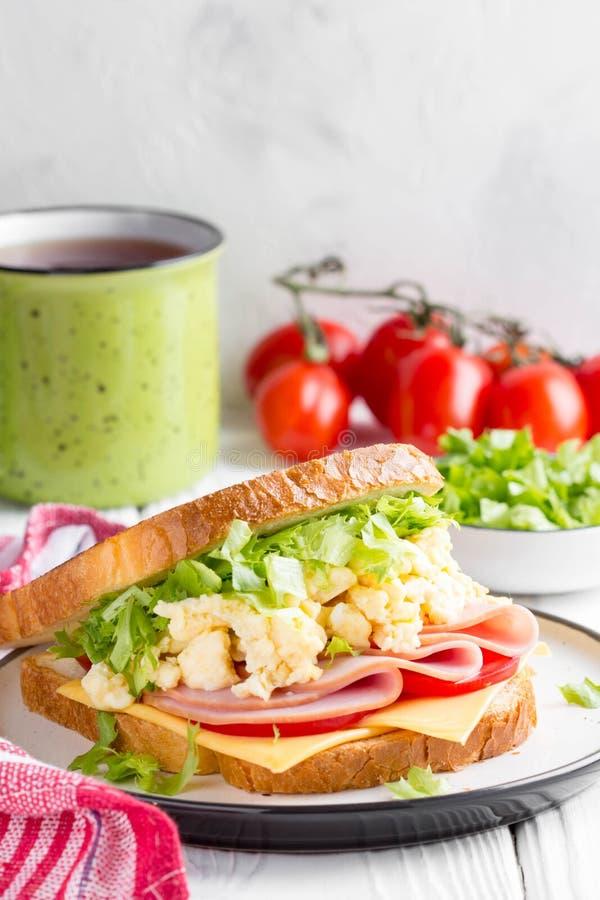 Sandwich au jambon avec l'oeuf brouillé, fromage, tomate, laitue, savoureuse photo libre de droits